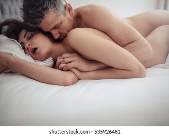 Naked couples making love in bedroom